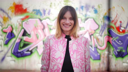 Model with pink dress posing in front of graffiti looking in camera and smiling