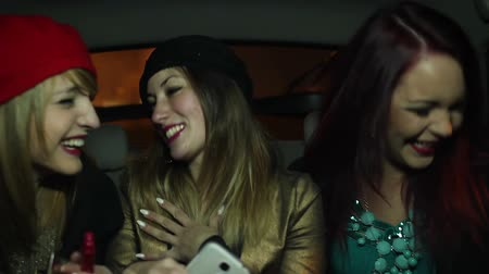 earings : Three young girls having fun and taking selfies in the back of a cab in the night time