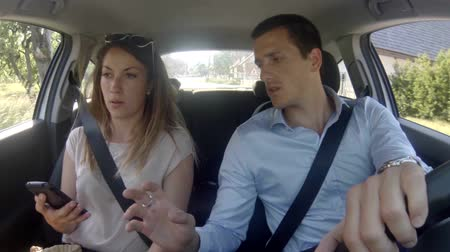 compromise : Couple in car quareling and texting sms on smartphone in the day