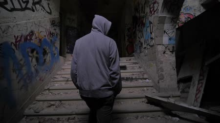 hátborzongató : Slow motion of a guy with hood walking through abandoned building