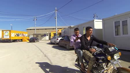 Iraqi Kurdistan slow motion of two guys driving a motorcycle into a IDP camp