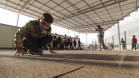 Iraqi Kurdistan teacher with kids during gym lesson in IDP camp school Stok Video