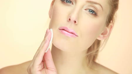 remover : Personal Hygiene And Healthcare, a beautiful blonde woman cleaning her face with a cotton pad.. Vídeos