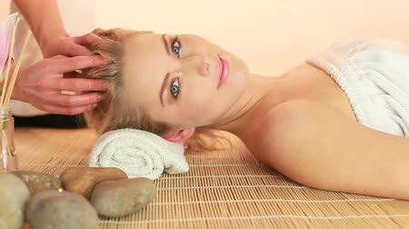 massages : Glamorous Woman Receiving Fingertip Head Massage, lying smiling on mat with masseuse hands only.