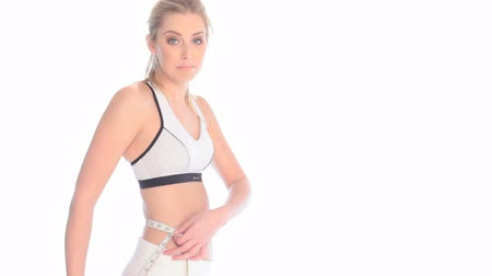 palce : Slender Young Woman Measuring Waist with tape facing sideways dressed in sportswear.