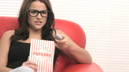 televízió : Young girl in glasses is eating popcorn and watching a movie