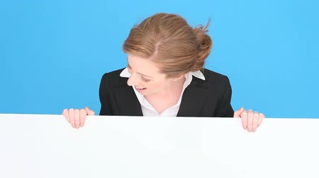 prapor : Smiling professional or businesswoman holding a large blank white sign, blue studio background