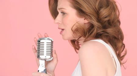 ruivo : Close-up image of the face of a female singer with her mouth open in song holding a microscope. Stock Footage