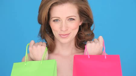 vöröshajú : Smiling Woman Shopper holding a red and green carrier bag to her chest, close-up head and shoulders on blue Stock mozgókép