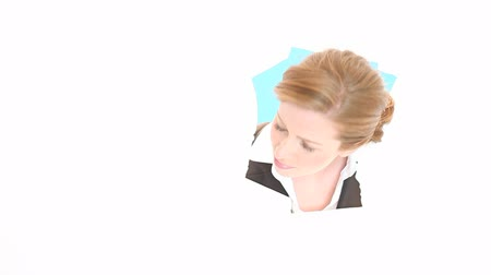 Łzy : A woman peers through a hole in a sheet of blank white paper which fills the frame. Wideo