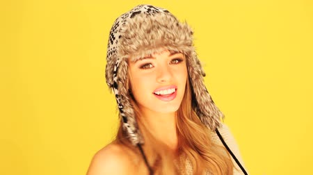 fiatal felnőttek : A stunning blonde woman wearing a winter fur hat with ear flaps isolated on a yellow studio background. Stock mozgókép