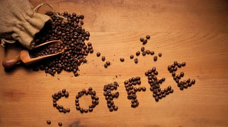 kahve çekirdeği : Fresh coffee beans spilling out of a sack onto a scoop with a the letters COFFEE on wooden background alongside.
