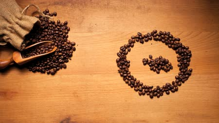 kahve çekirdeği : Fresh coffee beans spilling out of a sack onto a scoop with a pattern in the form of a face symbol on wooden background alongside. Stok Video
