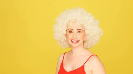amalucado : Humorous portrait of a young caucasian woman wearing a crazy white curly afro wig against a yellow studio background with copyspace.