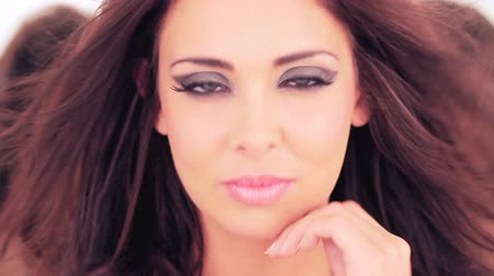 kadınlık : Beautiful woman with sultry eyes and a sensual expression wearing sexy makeup looking directlty into the camera Stok Video