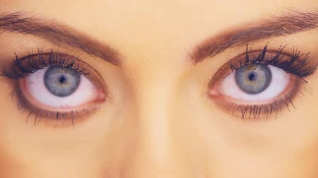 Close up detail of the wide blue eyes of a beautiful woman looking directly into the camera in a beauty portrait