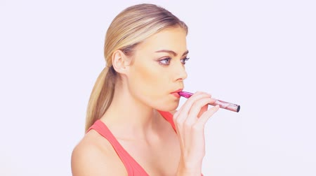 курильщик : Young woman smoking an e-cigarette holding the vaporizer in her hands as she exhales a puff of smoke