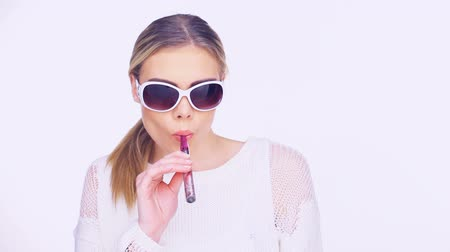 fumegante : Woman in trendy stylish glasses smoking an e-cigarette puffing out a cloud of smoke at the camera isolated on white