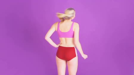tancerka : Happy beautiful woman in sports shorts with a bare midriff dancing on a purple background laughing and smiling at the camera with copyspace