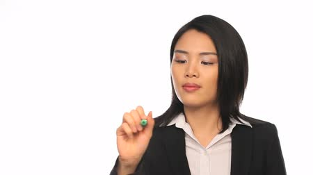 szemüveg : Attractive stylish young Asian businesswoman writing on a virtual screen interface with a pen against a white studio background