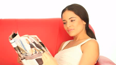 časopis : Attractive young brunette woman with a lovely smile reading a magazine reclining on a sofa