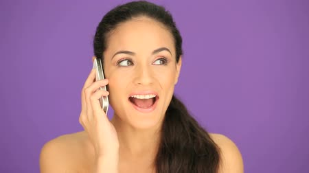брюнет : Attractive brunette woman with a lovely smile talking on her mobile phone against a purple background
