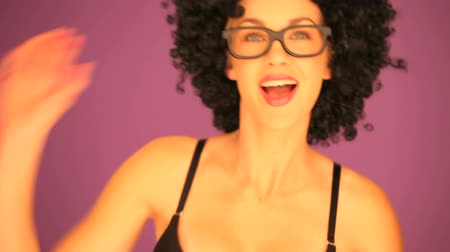 into focus : Woman with a large curly black afro hairstyle and glasses stepping into focus against a purple background