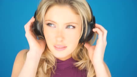 красивая женщина : Beautiful blond woman concentrating on her music listening intently to the soundtrack on her headphones, isolated on blue