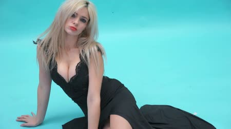 bra : sexy woman wearing long black dress sitting on the floor in a studio Wideo