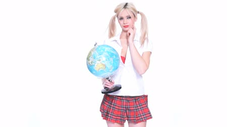 rövid : Beautiful cute young blond woman with her hair in pigtails wearing a short tartan skirt holding a globe against a white background with copyspace