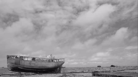 curvature : timelapse of the boat on the coast in uk , kent , dungness , moving sky