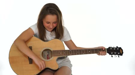 reklama : Young girl playing a wooden acoustic guitar strumming a tune on the strings, isolated on white