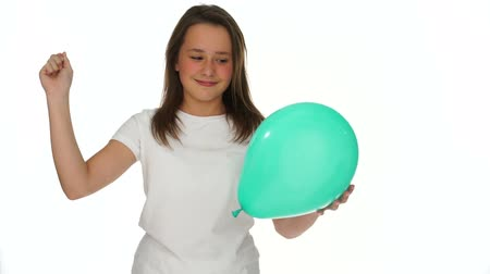 штифт : Playful attractive young girl about to prick a party balloon standing holding the balloon in one hand and a pin in the other with a smile of glee, on white