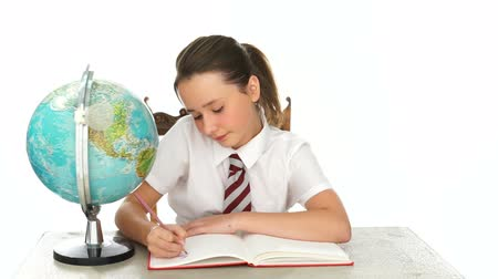 uniforme : Schoolgirl writing notes in geography class as she sits at her desk alongside a world globe Vídeos