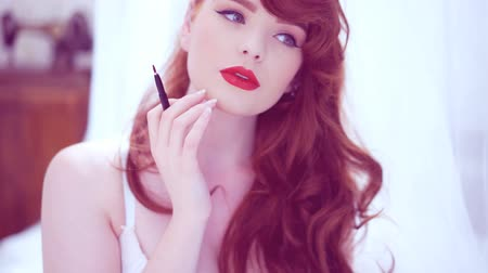 vöröshajú : beautiful redhead applying lipstick Stock mozgókép