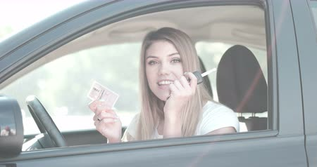 polegar : Beautiful young girl sitting in car showing driving licence new driver