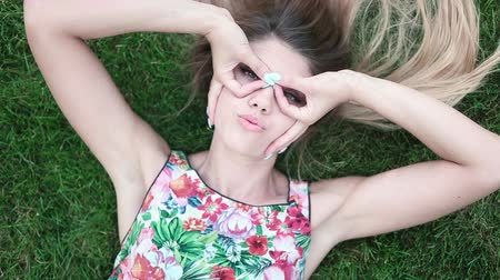 kıvırcık : happy woman wearing sunglasses woman lying on green grass Stok Video