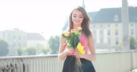 брюнет : happy brunette walking via the city with flowers