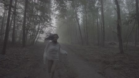 темно : Front view of beautiful woman in purple hair and white shirt running in forest - thriller scene. Video of sensual beauty between trees in slow motion, foggy and dark forest background.