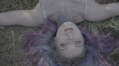 mese : Closeup of beautiful woman in purple hair falling down on the ground in forest - fairytale scene. Video of sensual beauty on green grass in slow motion. Stock mozgókép