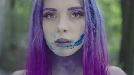yay : Close up of pretty woman in purple hair smudging her face with blue paint and looking at the camera. Isolated in forest, 4k video.