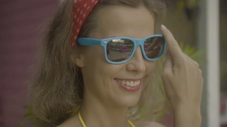 vestindo : Pretty young happy woman wearing bikini putting on sunglasses isolated on the background of pink house.