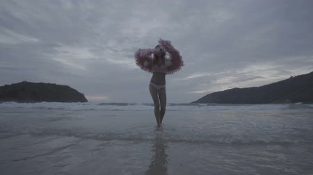 melek : Romantic young beauty as an angel on the beach. Blonde pretty female woman wearing pink wings, feather bra and bikni bottom smiling and walking in the sea over sky background - video in slow motion