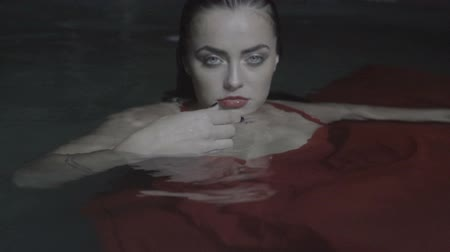 wampir : Closeup portrait of beautiful mysterious woman looking like a vampire wearing red dress standing in the pool and throwing playing card into the camera at night
