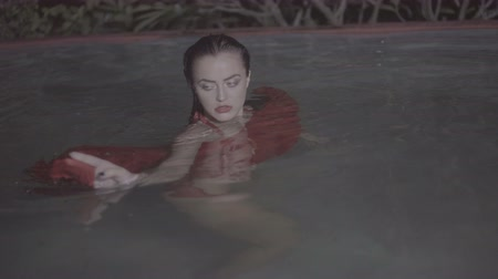 искушение : Closeup portrait of beautiful mysterious woman wearing red dress looking into the camera while dancing in the pool at night