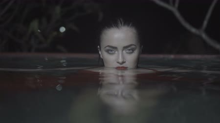 wampir : Closeup face and eyes of beautiful mysterious woman wearing red dress looking into the camera while swimming in the pool at night Wideo