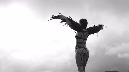 sobre o branco : Back view of beautiful seductive angel woman wearing lingerie and leather belts standing on the roof with wind in her wings over cloudy sky - black and white video