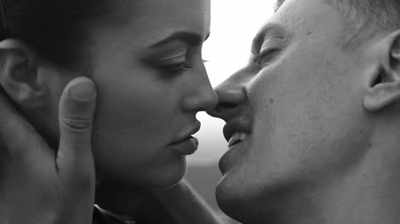 сексуальный : Black and white close-up video of romantic kiss between couple over sky background