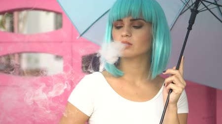 serseri : Sexy young girl in modern futuristic style with blue wig and umbrella smoking e-cigarette and puffing out cloud of smoke over pink wall background Stok Video