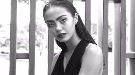 tmavé vlasy : Closeup face portrait of gorgeous fashion woman with dark hair in elegant black dress looking into the camera while sitting and posing on the bench over modern wall in tropical garden - black and white video in slow motion
